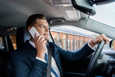 Businessman talking on mobile phone while driving car