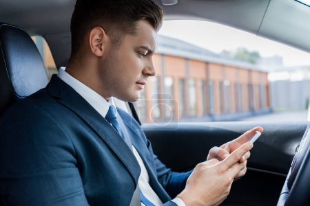 Businessman using smartphone while sitting on driver seat in car