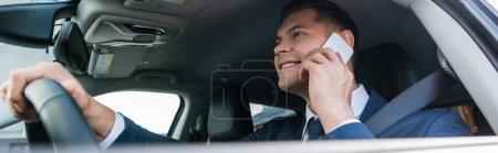 Positiver Geschäftsmann, der während der Autofahrt auf unscharfem Vordergrund mit dem Handy spricht, Banner