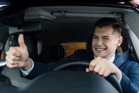 Lächelnder Geschäftsmann zwinkert und zeigt wie Geste beim Autofahren auf verschwommenem Vordergrund