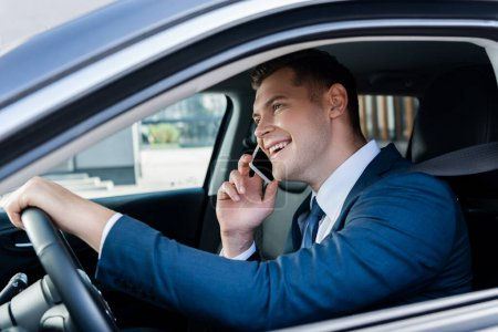 Photo for Smiling businessman talking on smartphone while driving car on blurred foreground - Royalty Free Image