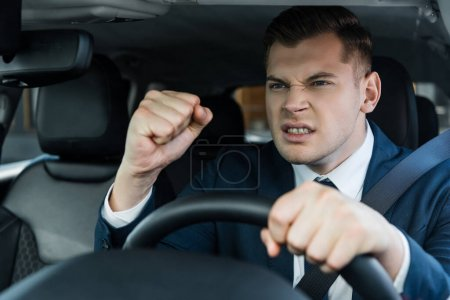 Angry businessman showing fist while driving auto on blurred foreground