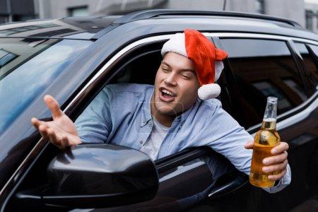 Photo pour Excité, homme ivre au chapeau de Père Noël, avec fiole d'alcool, geste en regardant par la fenêtre de la voiture - image libre de droit