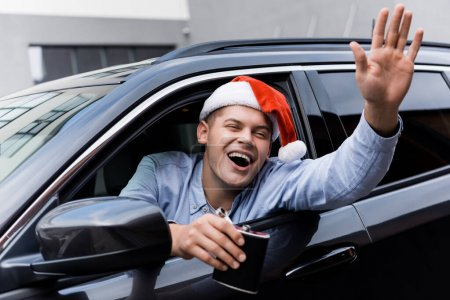 Photo for Drunk, excited man in santa hat waving hand and holding flask of alcohol while looking out car window - Royalty Free Image