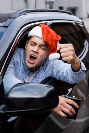Photo pour Homme agressif et ivre au chapeau de Père Noël, avec une fiole d'alcool, montrant le poing serré en regardant par la fenêtre de la voiture, au premier plan flou - image libre de droit