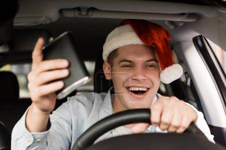 Photo pour Ivrogne, gai homme au chapeau de Père Noël tenant fiole avec de l'alcool tout en conduisant une voiture, au premier plan flou - image libre de droit