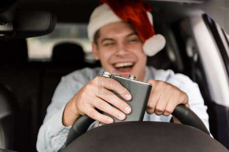 laughing, drunk man in santa hat holding flask with alcohol while driving car on blurred background