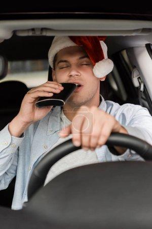 Betrunkener mit Weihnachtsmannmütze trinkt mit geschlossenen Augen aus Kolben, während er Auto auf verschwommenem Vordergrund fährt