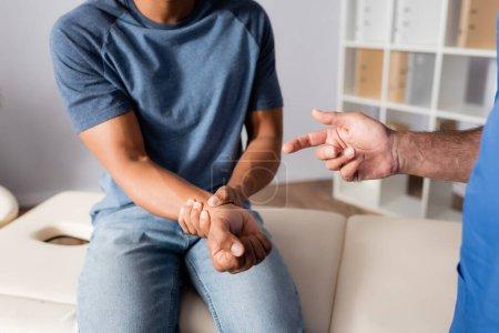 vue recadrée du chiropraticien pointant du doigt le bras blessé d'un patient afro-américain