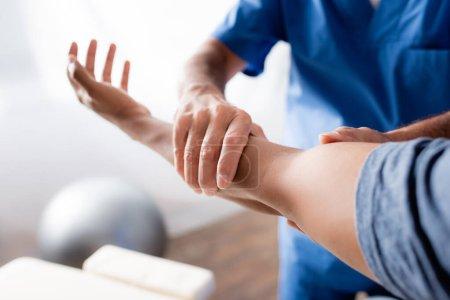 Photo pour Vue recadrée du chiropraticien travaillant avec le bras blessé de l'homme afro-américain en clinique - image libre de droit