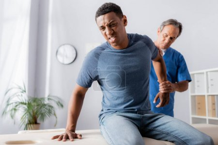 injured african american man suffering from pain near masseur on blurred background