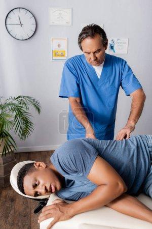 Foto de Quiropráctico de mediana edad que trabaja con paciente afroamericano en mesa de masaje - Imagen libre de derechos