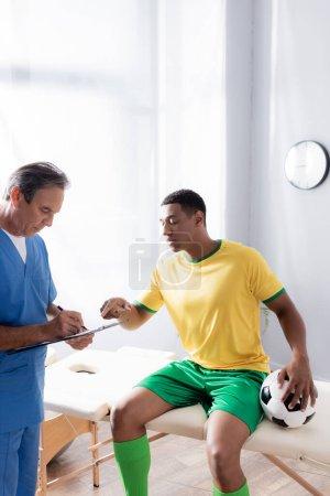 Arzt schreibt Rezept in der Nähe verletzter afrikanischer Fußballspieler sitzt mit Ball auf Massagetisch