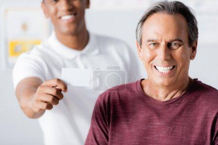 Photo pour Homme heureux souriant près de thérapeute afro-américain joyeux tenant carte blanche - image libre de droit