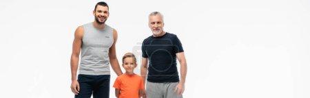 szczęśliwy dzieciak z dziadkiem i ojcem w odzieży sportowej uśmiechający się do kamery odizolowany na białym, baner