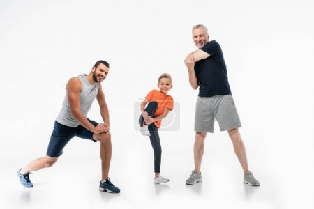boy with dad and grandpa in sportswear demonstrating power while smiling at camera on white