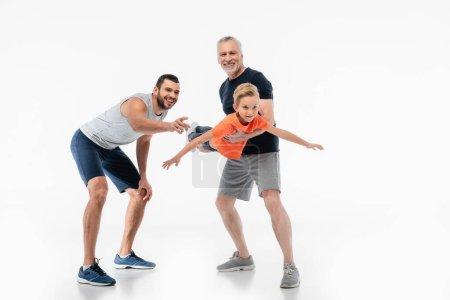 happy grandpa holding kid imitating flight near man pointing with finger on white