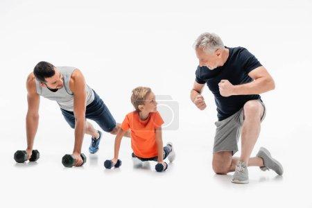Photo pour Heureux grand-père démontrant la force près de père et d'enfant faisant des pompes avec haltères sur blanc - image libre de droit