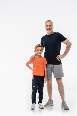 Lächelnder Großvater und glücklicher Enkel in Sportbekleidung, der in die Kamera auf Weiß blickt