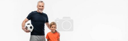 Photo for Cheerful man holding hand on shoulder of grandson while holding soccer ball isolated on white, banner - Royalty Free Image
