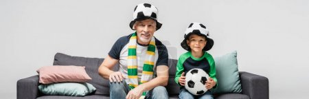 Photo for Cheerful grandfather and grandson in fan hats watching football match while sitting on sofa isolated on grey, banner - Royalty Free Image