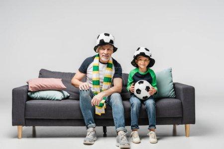abuelo sonriente y nieto viendo el partido de fútbol mientras está sentado en el sofá en sombreros de abanico en gris