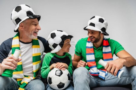 happy men in fan hats holding horns near boy with soccer ball isolated on grey
