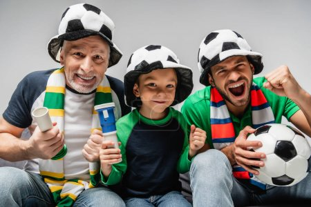 excited man screaming and showing win gesture near father and son in football fan hats isolated on grey