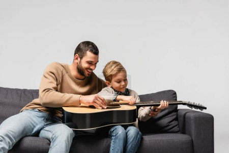 happy father teaching son playing acoustic guitar isolated on grey
