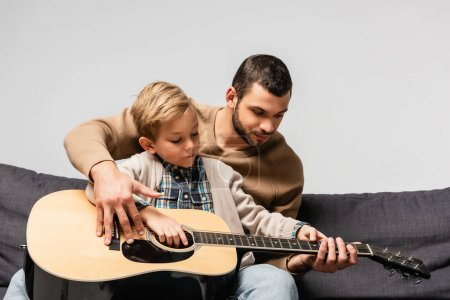 father teaching son playing acoustic guitar while sitting on sofa isolated on grey