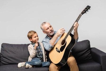 Photo pour Homme mature pointant du doigt la guitare acoustique près du petit-fils isolé sur gris - image libre de droit