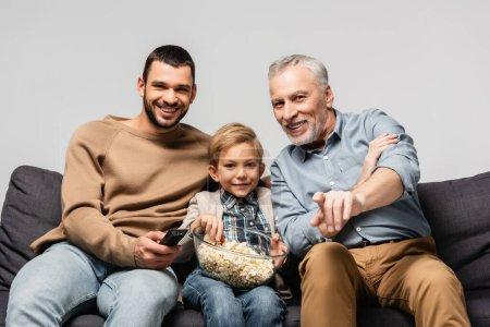Photo pour Sourire mature pointant du doigt tout en regardant la télévision près de fils et petit-fils isolé sur gris - image libre de droit