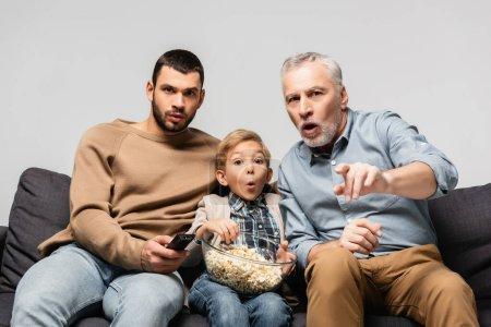 Photo pour Homme étonné pointant du doigt tout en regardant la télévision près de fils et petit-fils avec bol de maïs soufflé isolé sur gris - image libre de droit