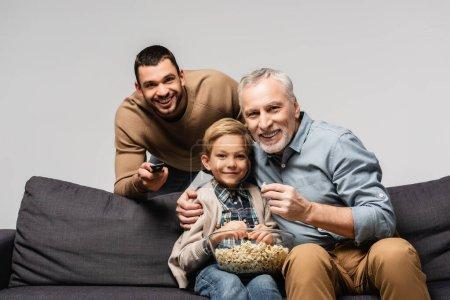 Photo pour Homme heureux tenant télécommande près de père et fils regarder la télévision et manger du maïs soufflé isolé sur gris - image libre de droit