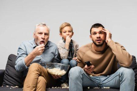 Photo pour Homme étonné tenant bol avec pop-corn tout en regardant la télévision avec fils et petit-fils isolé sur gris - image libre de droit