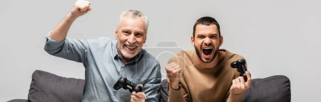 Photo for KYIV, UKRAINE - NOVEMBER 17, 2020: excited man with adult son showing win gesture while holding joysticks isolated on grey, banner - Royalty Free Image