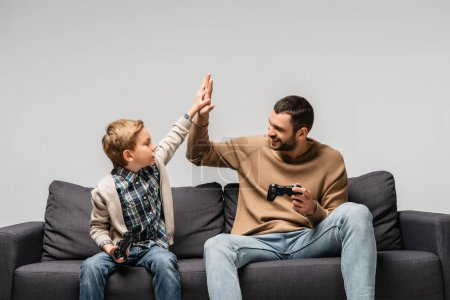 KYIV, UKRAINE - NOVEMBER 17, 2020: cheerful father and son holding joysticks and giving high five isolated on grey