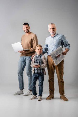 Photo pour Garçon gai tenant smartphone près de grand-père avec journal et papa avec ordinateur portable sur gris - image libre de droit