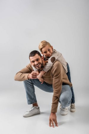Photo for Cheerful boy hugging happy dad while smiling at camera together on grey - Royalty Free Image