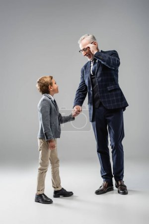 happy businessman touching eyeglasses while holding hands with grandson on grey
