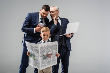 Photo for Mature businessman talking to son near boy in formal wear reading newspaper isolated on grey - Royalty Free Image