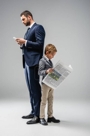 businessman messaging on smartphone while standing back to back with son reading newspaper on grey