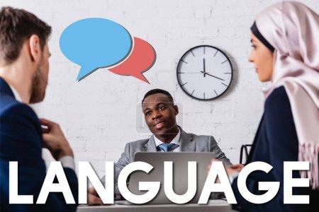 Photo pour Homme d'affaires afro-américain souriant près du traducteur et femme d'affaires arabe au premier plan flou, bulles d'expression et illustration de lettrage de langue - image libre de droit