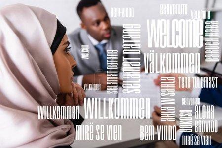 Photo pour Arabe femme d'affaires près de partenaires d'affaires multiculturels sur fond flou, mot de bienvenue dans différentes langues illustration - image libre de droit