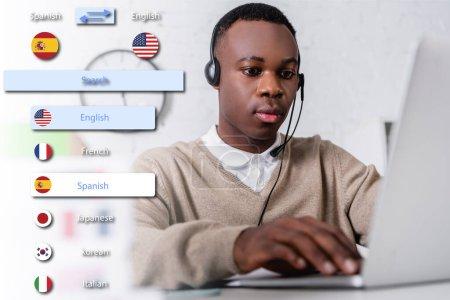 Photo pour Jeune interprète afro-américain en dactylographie sur ordinateur portable au premier plan flou, illustration de l'interface de l'application de traduction - image libre de droit