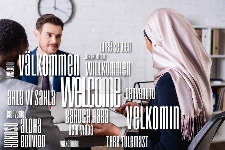 Photo pour Traducteur souriant près de partenaires d'affaires multiculturels au premier plan flou, mot bienvenu dans différentes langues illustration - image libre de droit