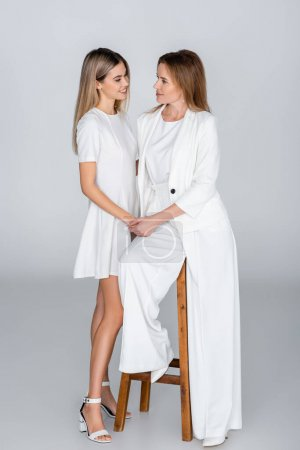 Photo pour Pleine longueur de la jeune fille et la mère regardant l'autre sur gris, génération de femmes - image libre de droit