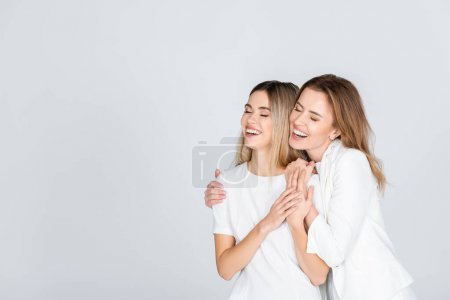 Photo for Happy mother hugging young daughter with closed eyes isolated on grey - Royalty Free Image