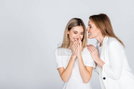 Photo for Cheerful mother whispering in ear of smiling daughter isolated on grey - Royalty Free Image