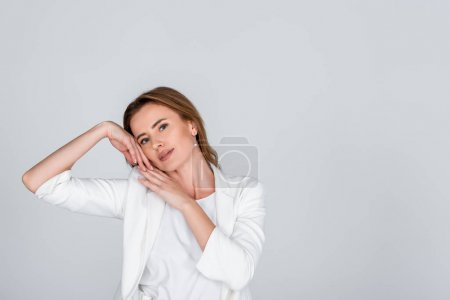 Photo for Woman in white outfit looking at camera while posing isolated on grey - Royalty Free Image